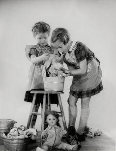 Huishouden, moedertje spelen, wassen, studio-opname. Twee meisjes met schorten voor, doen de poppenwas in een houten tobbe. Nederland 1950-1960.