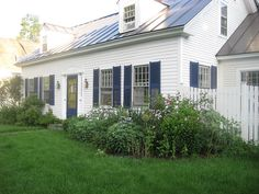 Navy blue shutters and door on a white house.  Very crisp.