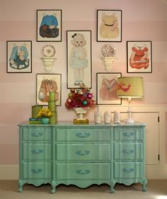 Adorable gallery wall of blown up paper dolls and their clothes w/cute painted blue antique dresser