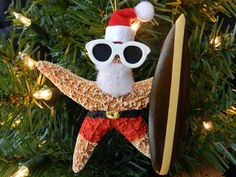 """This Santa starfish Christmas ornament is ready to hit the beach and catch some waves on his wooden surf board.  Sprouting a fuzzy white beard, red sunglasses and a classy black belt with a gold buckle, he is set for a day of sand and sun.  This starfish ornament is approximately 4"""" to 5.5"""".  It was hand painted and assembled in the United States."""