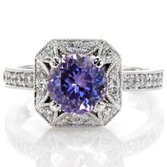 Sapphire Lotus - The Lotus Sapphire design is elegantly crated in 14k white gold and presents a rich, violet round cut natural sapphire. Elements of the ring include detailed prongs, hand applied milgrain and bright-cut bead-set diamonds. The square beveled edge halo is joined by a band of round diamonds.