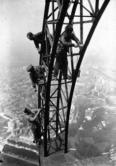 Painting the Eiffel Tower, Paris, 1932.