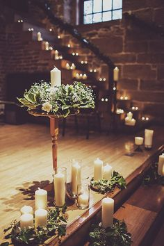 Add some vintage charm to a larger wedding venue using candles. This historic room is filled with greenery and large white candle decorations to give this ceremony space an intimate vibe.