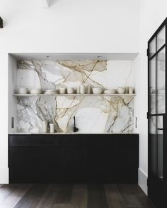 black cabinets, marble backsplash, floating shelf