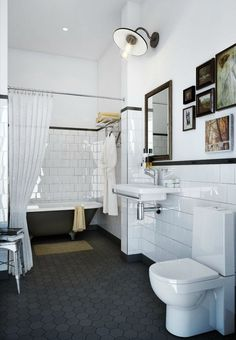 Black large hex tile + clawfoot tub + schoolhouse light + art