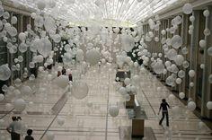 Centinaia di palloncini bianchi che fluttuano nell'aria e, manovrati dai passanti, creano un intenso paesaggio emotivo che diventa metafora di relazioni umane, di sentimenti, di distanza, di …