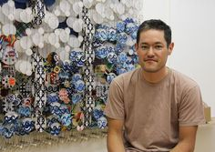 Portrait of American artist Jacob Hashimoto (b.1973) with his layered artwork 'superliner.'  Paper, bamboo, acrylic, dacron, 65 x 155 x 8 in. portrait © Design Boom