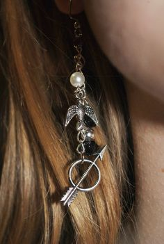 These earrings have Katniss' arrow, a mockingjay and Peeta's pearl dangling in silver. LOVE them!
