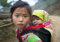 Flower Hmong girl and her baby sister - Vietnam An image i can see all aroud the world: as soon as the girl is strong enough to carry the last baby of the family, she takes care of him or her, while the mother works.