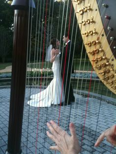 Leu Gardens wedding, Orlando, FL. Sweet photo with the bride and groom through the harp strings at a wedding ceremony in the Rose Garden.  #intimate #harpist #bride #groom #wedding #orlando