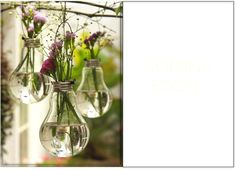 Hanging glass vases made out of old light bulbs.
