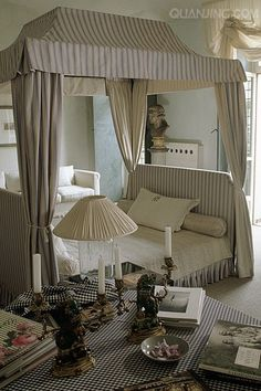 blue & white striped canopy bed in center of room