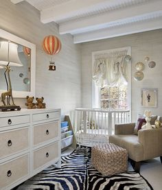 Neutral nursery, love the giraffe lamp, the hot air balloon toy and the planets hanging above the crib