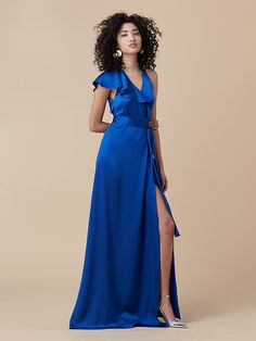 A sleek update to the traditional wrap style, this soft satin, sleeveless, floor-length dress is cut in a ravishing blue and features a cascading ruffle for compelling fluidity.