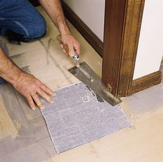 A step-by-step guide to preparing the floor and installing peel-and-stick tiles Retro Vinyl Flooring, Camper Flooring, Vinyl Tiles, Peel And Stick Floor, Peel And Stick Vinyl, Baseboard Molding, Baseboards, Bar Tile, Tile Cutter