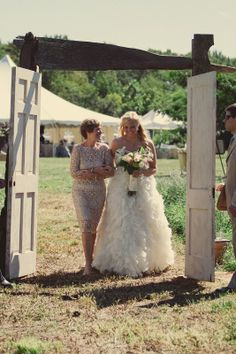 Tying the knot in the middle of a field didn't stop MaryKate from making a grand entrance through a doorway! Click on the image to see more of Mike and MaryKate's shabby chic DIY wedding day. | Photo by David Todd McCarty