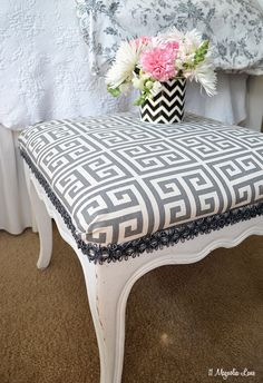 A vintage footstool is painted and updated with grey Greek key fabric and trim.  Easy DIY upholstery project.