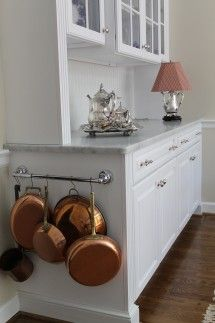CLEVER!!    A rail at the end of a cabinet is a perfect use of wasted space. Hang towels, pot holders or pans from it.