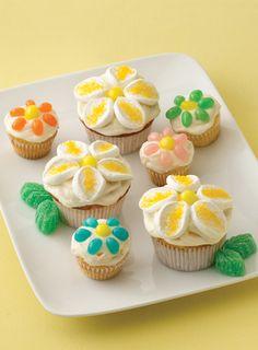 Crushed pineapple and orange marmalade bring a tropical twist to these pretty spring cupcakes. To make decorative daisies, arrange large marshmallow slices around candies and sprinkle with sugar.