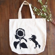 A Unicorn attacks a very large, but unsuspecting sunflower. Hand painted tote bag by Grafeeq Painted Bags, Hand Painted, Uni Bag, Cotton Tote Bags, Reusable Tote Bags, Gym Gear, Unicorn, Painting, Collection