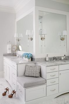 A built-in corner bench fitted with a single drawer adorned with a polished nickel pull topped with a gray cushion is flanked by his and her washstands topped with carrera marble placed under Camille Long Sconces mounted on thick, white framed vanity mirrors.