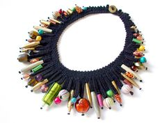 Fabric collar in black wool with a multitude of strung beads: polymer clay, paper wrapped and painted with acrylic gilding, aluminum made by Silvia Ortiz de la Torre and others bought wood, glass etc.