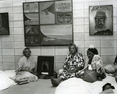 "Ans Westra Netta Wharehoka, Ngahina Okeroa and Materena Ran - Kupa from Taranaki sit with a photograh of Te Whiti at Selwyn Muru's exhibition opening - ""Parihaka"", The Dowse Art Museum, Lower Hutt, 1979 Silver gelatin print 212 x 255mm"