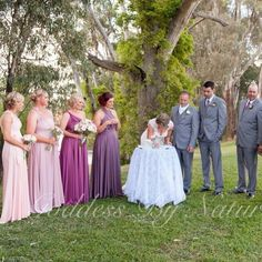 Beautiful newlyweds Bek with her husband & their bridal party at their outdoor garden ceremony all looking amazing! With their bridesmaids wearing Goddess By Nature dresses in a palette of gorgeous pinks & purple shades with groomsmen wearing their matching GBN mens ties!  www.goddessbynature.com #australiandesigner #weddinggown #countrywedding #outdoorwedding #multiwaydress #multifunctionaldress #1dressmanyways