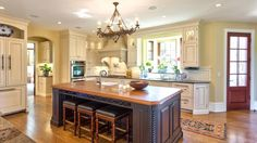 A dark brown island brings a grounding force to this otherwise light and airy traditional kitchen. Wood and leather stools can be pulled out to accommodate kitchen visitors or tucked neatly away.