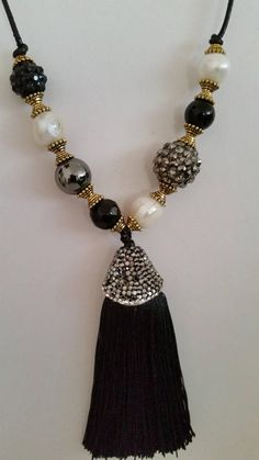 Short leather necklace and tassel pendant (Tassel) with imitation diamond Size: Length 17 inches or 43 cm and 3-inch or 7.5 cm extender chain Material: Leather, cultured pearls, tassel (tassel) with rhinestone Colors: white, black and grey Shipments: Worldwide Shipping to all over