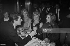 British actor Edmund Purdom (1924 - 2009, left) with Frances Shea (1943 - 1967, right), wife of English gangster Reggie Kray, at the El Morocco, a nightclub owned by the Kray Twins, in Soho, London, 30th April 1965. The Kray twins' mother, Violet Kray, is at centre (in dark dress), sitting to her right is Dolly Kray, wife of Charlie. Actress Adrienne Corri is at far left.