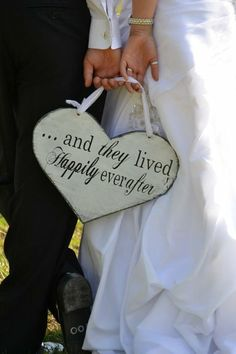 Bride and groom holding happily ever after sign.  See more castle wedding favors and party ideas at www.one-stop-party-ideas.com