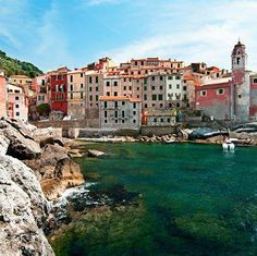 A jumble of pastel buildings cling to the cliffs of #Tellaro, #Italy, a true #Mediterranean haven.