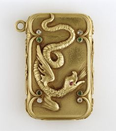 Rectangular, with rounded corners, featuring raised decoration of winged dragon with long, serpent-like tail that curls and extends up onto lid. Dragon has single red ruby for eye. Creature is framed on right and left by raised vertical bands; their ends curve inward and terminate with emeralds at each point. Above right and left, on lid, and below on lower section of box, are short, raised, curved bands that terminate at a single point with diamonds, each point abutting one of the four…