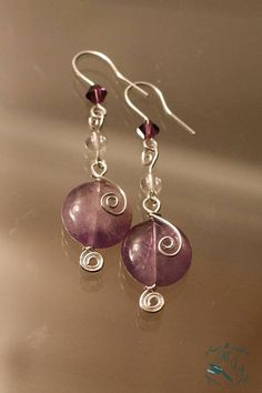 natural amethyst stone - silver-plated - stone: approx. 0.5 in / 1.25 cm - whole earring: 2 in / 5 cm Amethyst is not only the February birthstone, but also a coveted violet variety of quartz, and in these earrings the stone is accented by small matching glass crystal beads.