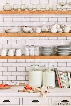 Lauren Conrad's kitchen with subway backsplash, floating wooden shelves, china, and cookbooks