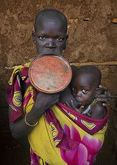 Suri Tribe Woman With A Lip Plate And Her Baby, Kibish, Omo Valley, Ethiopia (Eric Lafforgue) Tags: africa portrait people baby color love beauty vertical wall proud outside photography interesting colorful day serious outdoor body decoration mother bald culture pride jewelry tribal ornament clay adobe intriguing omovalley breastfeeding tradition ethiopia tribe pastoral shavedhead ethnic groupofpeople surma bizarre impressive bodymodification jewel labret confidence hornofafrica…