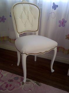 Cadira blanca, tapissada en blanc, xapes daurades.