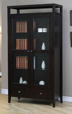 This Aristo brown wood cabinet is constructed of sturdy and durable hardwood with a rich, dark brown finish. This tall cabinet features four adjustable shelves behind two glass doors for storage space customization and a bottom drawer.