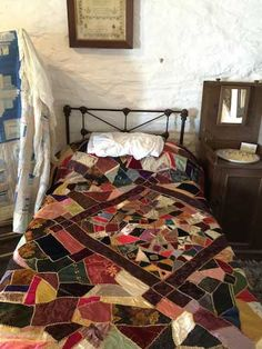 Wow, that looks really good in that setting ... that iron bedstead.  [victorian crazy quilt on a bed]