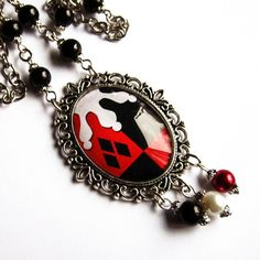 Harley Quinn inspired Necklace with glass cabochon. Comes with a sturdy chain with black and dark red glass beads and a quality lobster claw clasp. Size of the pendant is 45 x 56 mm, and features 3 glass bead pendants.