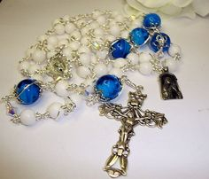 Sterling silver crucifix and center, white jade and blue lampwork beads. All wire wrapped in fine silver plated wire. $218.00