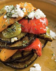 Eggplant and Peppers with Feta -- Stack grilled eggplant between layers of red, yellow, orange, and green bell peppers, then garnish with marjoram and feta cheese.