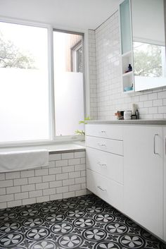 A graphic black and white floral patterned floor tile is paired with classic white subway tiles with grey grout.