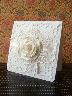all whte with lacy die cut layers, a satin riibbon, and a large rolled rosed as a center point...beautiful!!