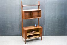Denmark, c.1961. HG 70 Wall Unit Bookshelf Cabinet in Teak by Thygersen & Sørensen. Tambour Door Lower storage cabinet opens to Adjustable Shelf, 2 Bay Open Cabinet with Sliding Glass, Adjustable Glass Shelves, Narrow Top Shelf. Integrated Peg Rails on Rear and Sides Allowing Expandability for other HG System Modules. Marked with Metal Danish Control Medallion. In Excellent Vintage Condition.    W: 36½ x D: 18 x H: 79¼ in.  *(Cabinet H:15½, Glass Cabinet H: 14, Top Shelf D: 9 in.)