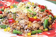 Uvařená pohanka promíchaná s podušenými kousky masa a zeleniny, rizoto na talířích ozdobené nastrouhaným tvrdým sýrem.