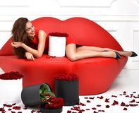 Woman lying on red lips sofa couch and red dress with roses bouq Royalty Free…