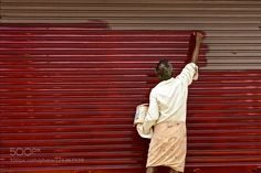 Paint me red A painter going about doing his job in Kollam Market in India