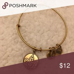 Alex & Ani Gold Tone Fleur-de-lis Charm Bracelet Alex & Ani gold tone fleur-de-lis charm bracelet. I'm selling this because I do not wear bracelets anymore. I usually ship same day or the next day! Price is basically firm but feel free to message me if you have any questions !! :)) Alex and Ani Jewelry Bracelets